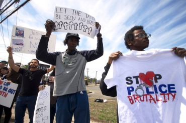 "NYC Activist Marcus from Picture The Homeless holds up a sign. NYC activist Prince from Justice Committee stands next to him, holding up the Justice for Kenny Coalition ""Stop Police Brutality"" tee shirt. Annual Anti-Police Brutality March in Long Island, April 12th, 2014, Bay Shore, New York."