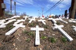 31 white crosses spread out on the lawn by the Suffolk County 3rd Precinct, each cross representing a life who died at the hands of Long Island police. Annual Anti-Police Brutality March in Long Island, April 12th, 2014, Bay Shore, New York.