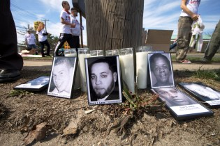 Printed photos of Long Island Stolen Lives (killed by Law Enforcement) and candles sit on the side of the Suffolk County 3rd Precinct where Kenny Lazo, Annual Anti-Police Brutality March in Long Island, April 12th, 2014, Bay Shore, New York.