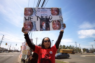 Angie Hicks, aunt of Police Brutality victim, Shantel Davis of Brooklyn, holds a sign demanding justice for Kenny Lazo at the Annual Anti-Police Brutality March in Long Island, April 12th, 2014, Bay Shore, New York.