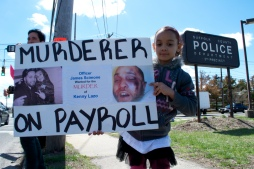 Elliana holds a protest sign, Annual Anti-Police Brutality March in Long Island, NY, Bay Shore, April 13th, 2013.