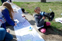 Elliana practices chants on the bullhorn while others write on the banner, Annual Anti-Police Brutality March in Long Island, NY, Bay Shore, April 13th, 2013.