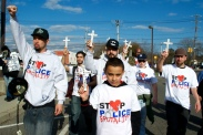 The group marches with the crosses to the precinct doors. Protesters march down 5th Avenue, demanding justice for police brutality victims. Annual Anti-Police Brutality March in Long Island, NY, Bay Shore, April 13th, 2013.